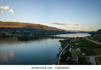 Aerial panoramic view of a small town, Oyama, during a vibrant summer sunset. Located near Kelowna and Vernon, BC, Canada.