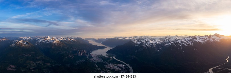 Aerial Panoramic View of a small Town surrounded by Canadian Mountain Landscape during a colorful sunset. Taken in Squamish, North of Vancouver, British Columbia, Canada.