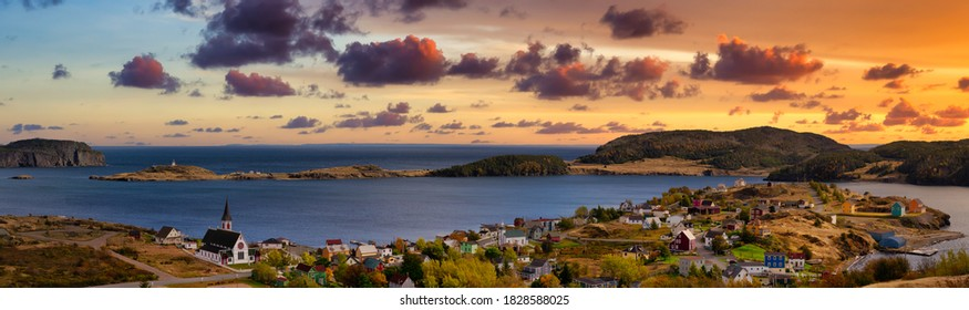 Aerial panoramic view of a small town on the Atlantic Ocean Coast. Dramatic Colorful Twilight Sky. Sunset or Sunrise. Taken in Trinity, Newfoundland and Labrador, Canada. - Shutterstock ID 1828588025