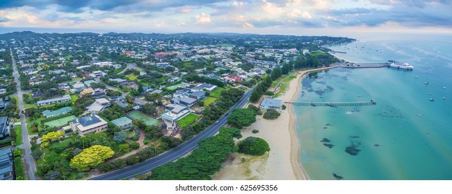 Aerial panoramic view of Sorrento Long Pier, moored passenger ferry and Point Nepean Road at dawn.  Mornington Peninsula, Melbourne, Australia