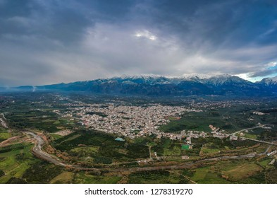 Aerial panoramic view of Sparta city with the snowy Taygetus mountain in the background and Eurotas river in the foreground against a cloudy sky.
