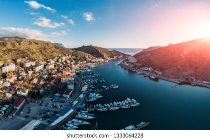 Aerial panoramic view of sunset over Balaklava, Crimea sea bay with many yachts and boats in resort coast between mountains. Beautiful tourist luxury European sunny town with harbour