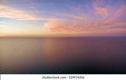 Aerial panoramic view of sunset over ocean. Nothing but sky, clouds and water. Beautiful serene scene