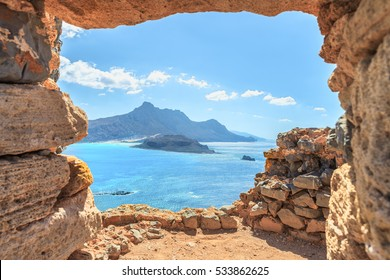 Aerial panoramic view through stone arch of an ancient Venetian castle on the beautiful beach at Balos lagoon ( famous world landmark ). Island of Imeri Gramvousa next to Crete .Chania. Greece. Europe