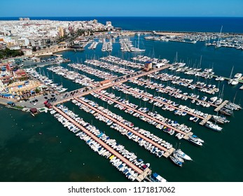 Aerial panoramic view of Torrevieja cityscape and marina port. Nautical vessel, yachts, motoboats moored in harbor in Mediterranean Sea. Torrevieja is Mediterranean city, Alicante. Costa Blanca. Spain