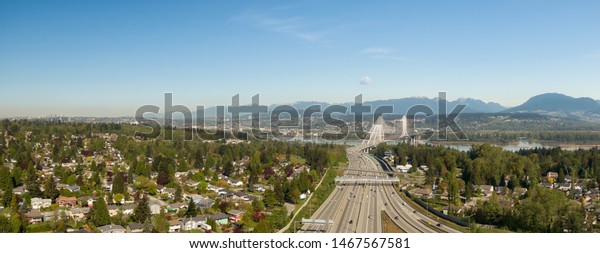 Aerial panoramic view of Trans Canada Highway near the Port Mann Bridge during a sunny morning. Taken in Surrey, Vancouver, BC, Canada.