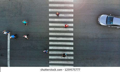 Aerial. Pedestrian crossing crosswalk. People group moving. Car stopped behind a crosswalk.