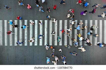 Aerial. People crowd on a highway pedestrian crosswalk.