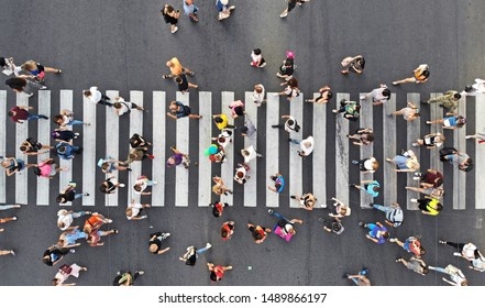Aerial. People crowd on pedestrian crosswalk. Top view from drone.