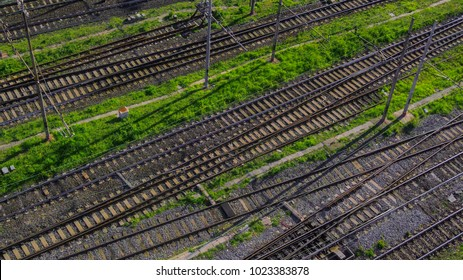 Aerial perpendicular view of the tracks of a train station passing by a road where there are cars parked. A few bushes of grass grows between the rails. There is nobody.