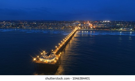 Aerial perspective of Oceanside pier in north county San Diego at dusk with light reflecting and glowing on the Pacific Ocean