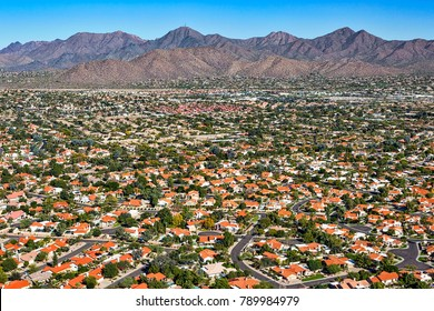 Aerial perspective of an upscale southwest suburban neighborhood with a scenic mountain backdrop