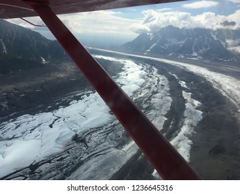 Aerial perspective view of curved glacial path as seen through wing of prop plane in mountains in Alaska