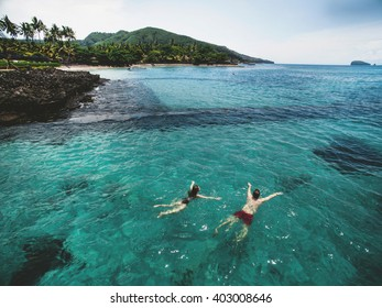 Aerial photo from above of beautiful young couple swimming in the ocean at the tropical island beach