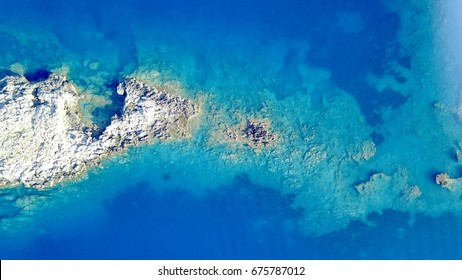 Aerial photo above rock reef crystal clear blue sea water