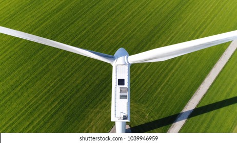 Aerial photo above wind turbine in polder landscape showing the white modern construction of the wind turbine device that converts winds kinetic energy into electrical energy