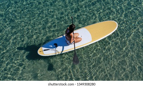 Aerial photo of attractive fit young woman practicing stand up paddle board or SUP in tropical caribbean sapphire crystal clear sandy exotic beach