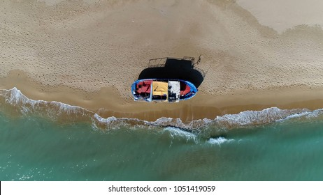 Aerial photo of azure blue ocean stranded refugee boat at southern mediterranean beach showing the colorful vessel located at the yellow beach with human footprints also showing the azure blue ocean