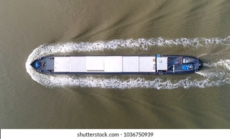 Aerial photo of barge moving over canal this flat-bottomed boat is mainly built for river and canal transport of heavy goods most barges are self-propelled