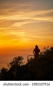 Aerial photo of bearded man on a cliff enjoying sunset