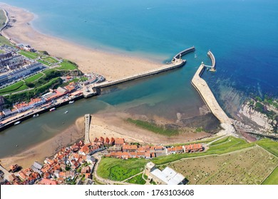 Aerial photo of the beautiful town of Whitby in the UK in North Yorkshire in the UK showing the beach and harbour on a hot sunny summers day