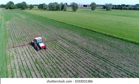 Aerial photo corn field tractor spraying agrochemical or agrichemical over young maize field in most cases agrichemical refers to pesticides like insecticides herbicides fungicides and nematicides