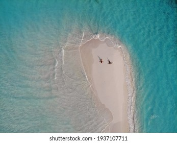 Aerial photo of couple laying on sandbank with turquoise water. Drone picture of two people on white sand on lonely island, Maldives, Indian Ocean. Isolation in tropical paradise.
