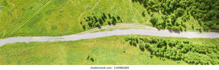 Aerial photo of the dirt road in a partially wooded countryside field