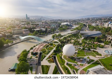 Aerial photo. Drone flies above Tbilisi Georgia city center. Rike park, river kura, futuristic Exhibition hall and Music concert. Bridge of peace. Air balloon. Beautiful old city panorama
