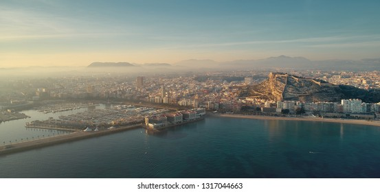Aerial photo drone point view Alicante cityscape above panorama main landmark in city center Santa Barbara castle on Mount Benacantil moored yachts in the harbour Mediterranean sea at sunset, Spain