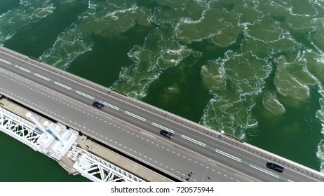 Aerial photo of Eastern Scheldt storm surge barrier Oosterscheldekering top-down view showing traffic driving over largest of 13 Delta Works series of dams and storm surge barriers Zeeland Holland