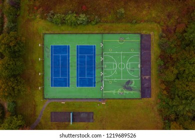 Aerial photo of empty tennis and basketball courts surrounded by autumn colors