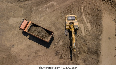 Aerial photo of excavator pours sand into the truck. On the construction site top view. Shooting from the drone/