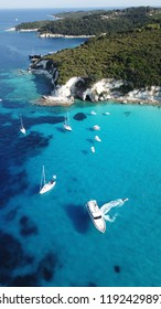 Aerial photo of exotic bay with sail boats and luxury yachts enjoying deep turquoise mediterranean sandy beach