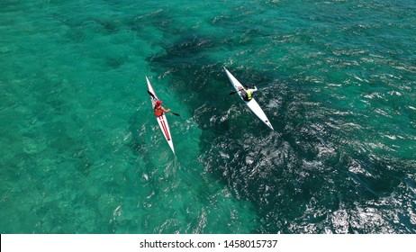 Aerial photo of fit athletes competing on sport canoe in tropical exotic bay with crystal clear turquoise sea