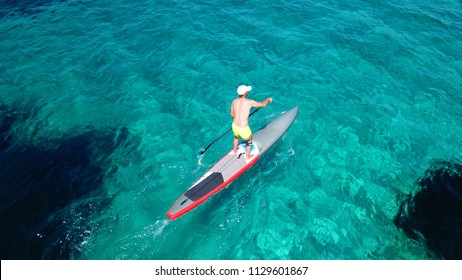 Aerial photo of fit man exercising SUP or Stand Up Paddle board in turquoise clear mediterranean island