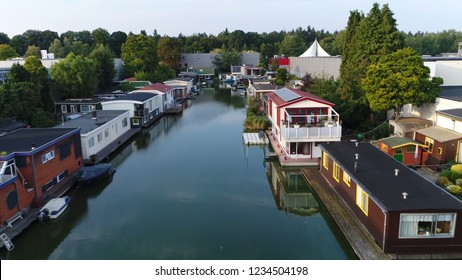 Aerial photo of fixed houseboats on left and right side of shore typical dutch type of wooden living boats