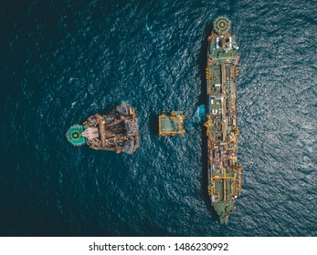 Aerial photo of Floating Storage Unit, a wellhead platform and drilling rig at oil field.