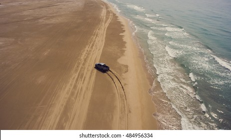 Aerial photo from flying drone of a riding pickup machine on a sandy beach near sea with beautiful waves. Active sport leisure on a rental car near Indian Ocean during amazing trip to Thailand