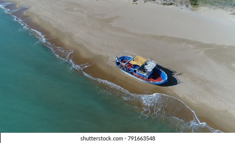 Aerial photo of front side of stranded refugee boat on mediterranean beach showing azure blue ocean waves and peaceful beach with human footprints around the stranded ship taken during refugee crisis