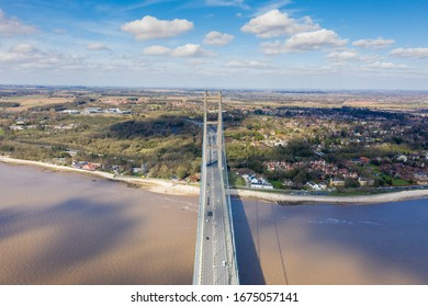 Aerial photo of The Humber Bridge, near Kingston upon Hull, East Riding of Yorkshire, England, single-span road suspension bridge, taken on a sunny day with a few white clouds in the sky.