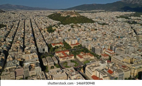 Aerial photo of iconic landmark neoclassic buildings of Academy, University and public Library and Lycabettus hill at the background in the heart of Athens historic centre, Attica, Greece