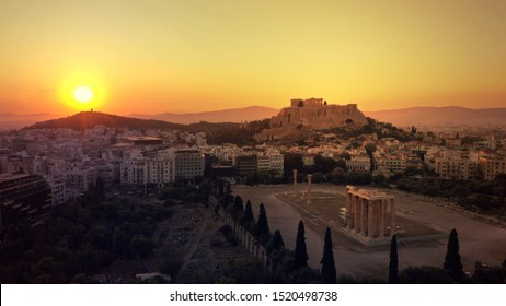 Aerial photo of iconic pillars of Temple of Olympian Zeus and Acropolis hill at the background with beautiful golden colours at sunset, Athens historic centre, Attica, Greece