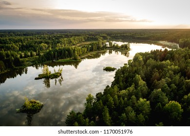 Aerial photo of the lake in the forests in sunset. Lake with small islands