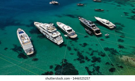 Aerial photo of luxury speed boats and yachts docked in popular beach of Psarou with iconic resorts, Mykonos island, Cyclades