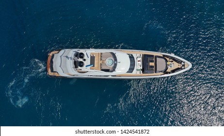 Aerial photo of luxury yacht with wooden deck docked in island of Mykonos deep blue sea of Super Paradise, Cyclades, Greece