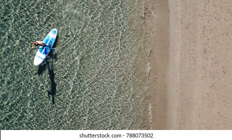 Aerial photo of man with his sup paddle board in coast of caribbean clear sandy seascape