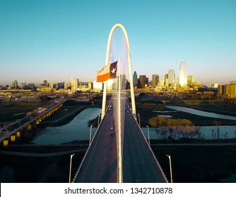 Aerial photo of Margaret Hunt Hill Bridge with Dallas city skyline in background at sunset
