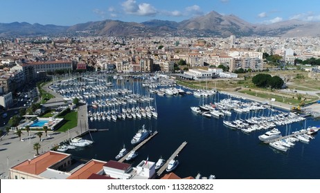 Aerial photo of marina yacht club located at Palermo Sicily Italy showing streets on left and harbor on right furthermore showing the city center and mountains in background