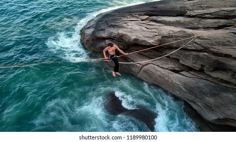 Aerial Photo of Mindfulness Scenery: a Boulder With Brazilian Atlantic Ocean Cliff and a Young Bravery Man Sitting on a Tightrope, Waterline Chalenge in a Secret Paradisiac Beach of Rio de Janeiro